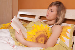 Young blond woman reading book in bed Stock Photo