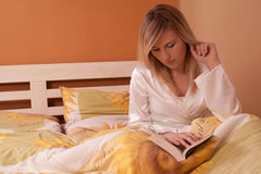 Young blond woman reading book in bed Stock Photos