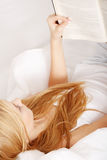 Young blond woman reading book on the bed Royalty Free Stock Photos
