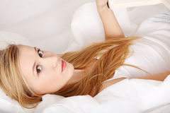 Young blond woman reading book on the bed Stock Photography
