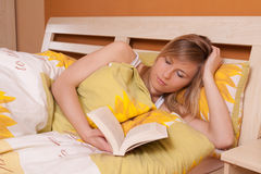 Young blond woman reading book in bed (up view) Royalty Free Stock Photo