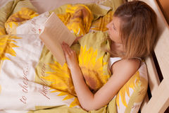 Young blond woman reading book in bed (up view) Royalty Free Stock Image