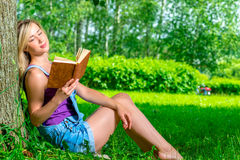 Young blond woman reading a novel in the park Stock Photos