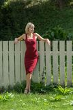 Young blond woman in a red dress leaning against the wooden fence. 