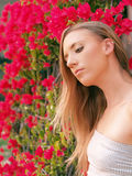 Young blond woman with red flowers in background Royalty Free Stock Photos