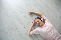 Young blond woman relaxing on the floor listening to music Stock Photo