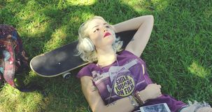 Young blond woman relaxing listening to music. Pretty young blond woman relaxing on lush green grass in the shade of a tree in summer listening to music lying stock video footage