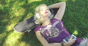 Young blond woman relaxing listening to music. Pretty young blond woman relaxing on lush green grass in the shade of a tree in summer listening to music lying stock footage