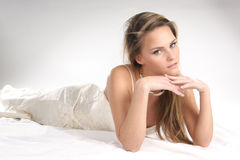 A young blond woman is relaxing in a white dress Stock Image