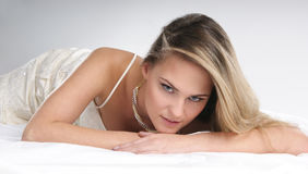 A young blond woman is relaxing in a white dress Royalty Free Stock Photos