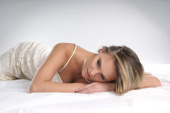 A young blond woman relaxing on a white silk bed Stock Images