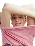 Young blond woman removing outer shirt smiling Royalty Free Stock Image