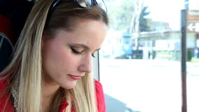 Young blond woman riding tram, looking down stock video footage