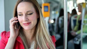 Young blond woman riding tram, talking on phone and playing with hair stock video footage
