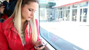 Young blond woman riding tram, typing on mobile, phone, cell stock video