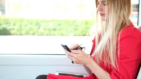 Young blond woman riding tram, typing on mobile, phone, cell stock video footage