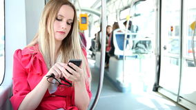 Young blond woman riding tram, typing on mobile, phone, cell, holding glasses stock video footage