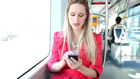 Young blond woman riding tram, typing on mobile, phone, cell and talking stock video footage