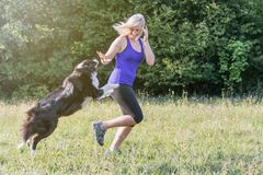 Young blond woman is running with her dog stock photography