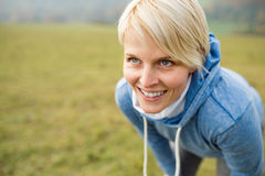 Young blond woman running outside in sunny nature, resting. Young blond woman in blue sweatshirt with hood, breathing hard after running outside in sunny nature Stock Images