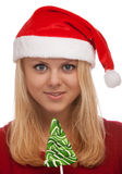 Young blond woman in santa hat with candy Royalty Free Stock Images