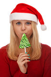 Young blond woman in santa hat with candy Royalty Free Stock Photo