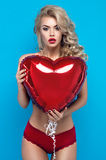 Young blond woman in sexy lingerie with heart balloon Royalty Free Stock Photos