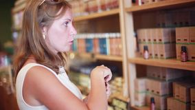 Young blond woman shopping smelling aroma oil in store. 1920x1080 stock footage