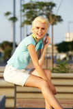Young blond woman with short hair smiling outside Stock Photography