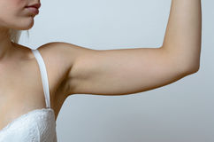 Young blond woman showing flabby arm Stock Images