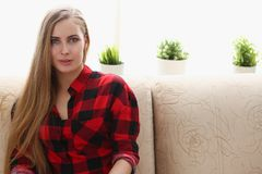 Young blond woman sit on sofa in room. Early morning. dreaming interior pleasure concept Stock Photography