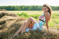 Young blond woman sits on hay Royalty Free Stock Photo