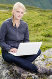 Young blond woman sits with a laptop on a stone Royalty Free Stock Photography