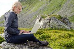 Young blond woman sits with a laptop on a stone Stock Photo