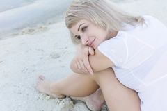 Young blond woman sitting on the beach and dreaming, close portrait. Young blond woman sitting on the beach and dreaming, lonely and pretty, close portrait Stock Photo