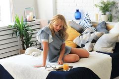 Young blond woman sitting on bed with notebook and a glass of juice, freelancer at home stock image