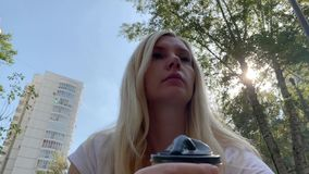 Young blond woman sitting on the bench in summer city park and drinking coffee disposable paper takeaway cup with a. Black human face form cup stock footage
