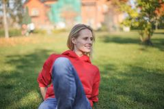 Young blond woman is sitting on the grass in the park. She is chilling out stock photos