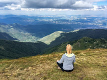 Young blond woman sitting meditating a mountain view. Young blond woman sitting, meditating on a grassy plateau admiring a mountain view with peaks and forested stock photo