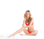 A young blond woman sitting in red erotic lingerie Stock Photo