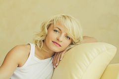 Young blond woman sitting on the sofa Stock Images
