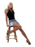 Young blond woman sitting on stool long bare legs. Young woman in jeans skirt showing bare legs Royalty Free Stock Photo