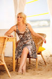 Young blond woman sitting in a wicker chair Royalty Free Stock Image