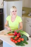 Young blond woman slicing vegetables on kitchen Stock Photo
