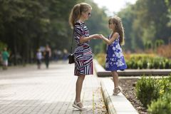 Young blond woman and small child girl in fashionable dresses holding hands on sunny park alley. Profile full-length portrait of young blond long-haired stock photo
