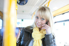 Young blond woman with a smart-phone inside a bus Royalty Free Stock Images