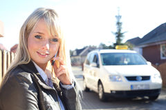 Young blond woman with smartphone and taxicab Stock Photos