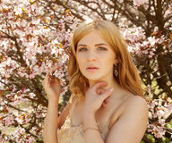 Young blond woman smelling flowers Royalty Free Stock Photos