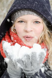Young blond woman blows in a handful of snow Royalty Free Stock Image
