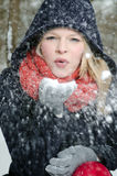 Young blond woman blows in a handful of snow Royalty Free Stock Photo
